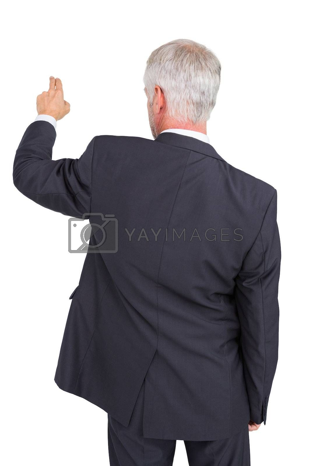 Rear view of stylish mature businessman pointing finger by Wavebreakmedia