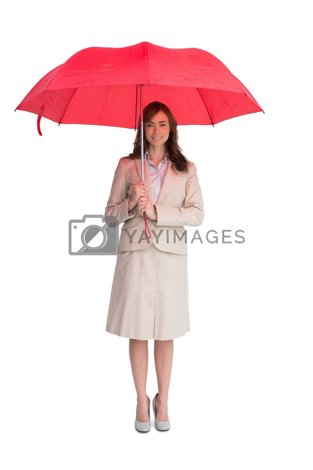 Attractive businesswoman holding red umbrella by Wavebreakmedia