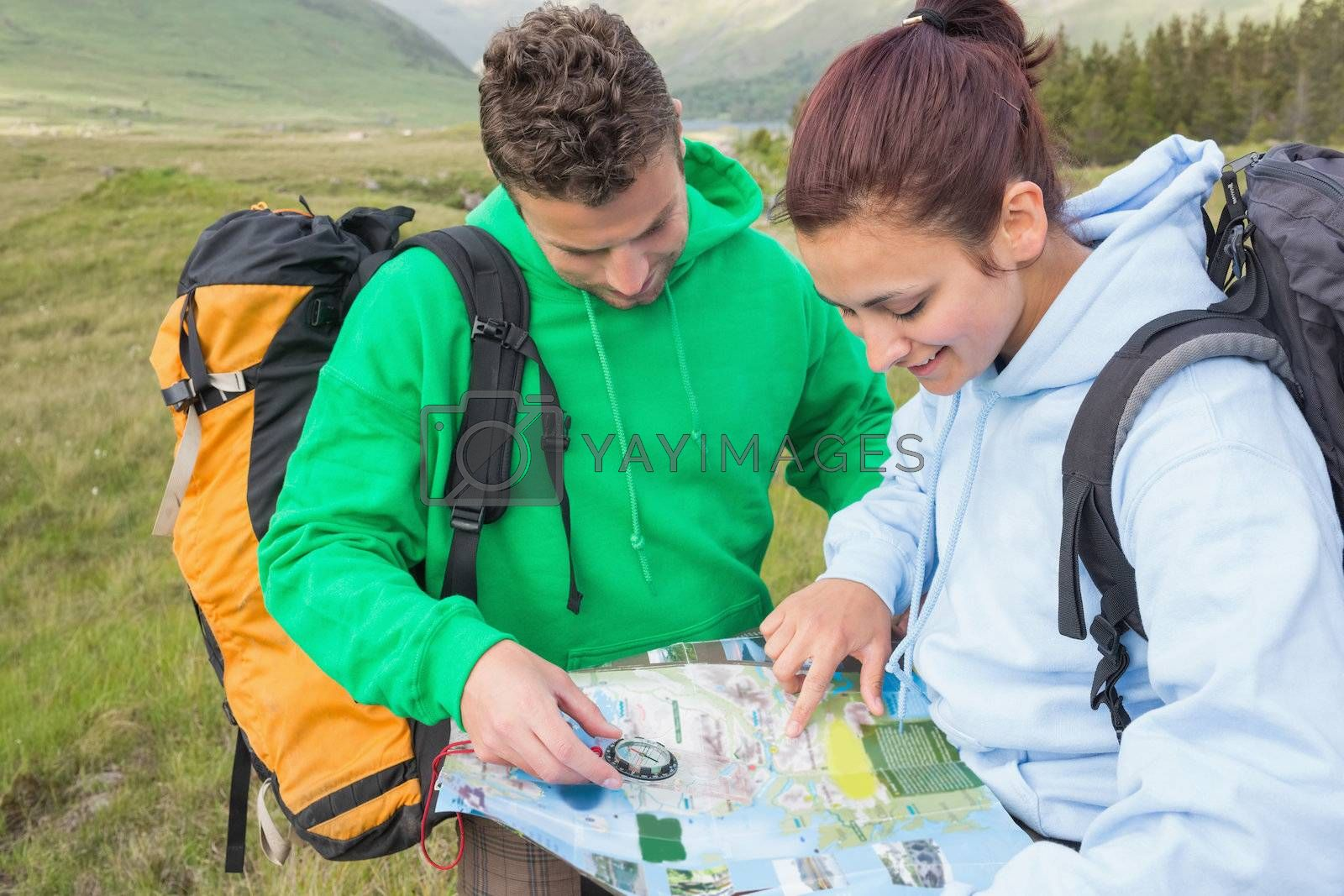 Couple sitting after hiking uphill and consulting map by Wavebreakmedia