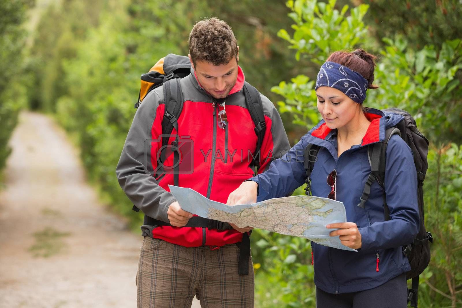 Happy couple going on hike together looking at map by Wavebreakmedia