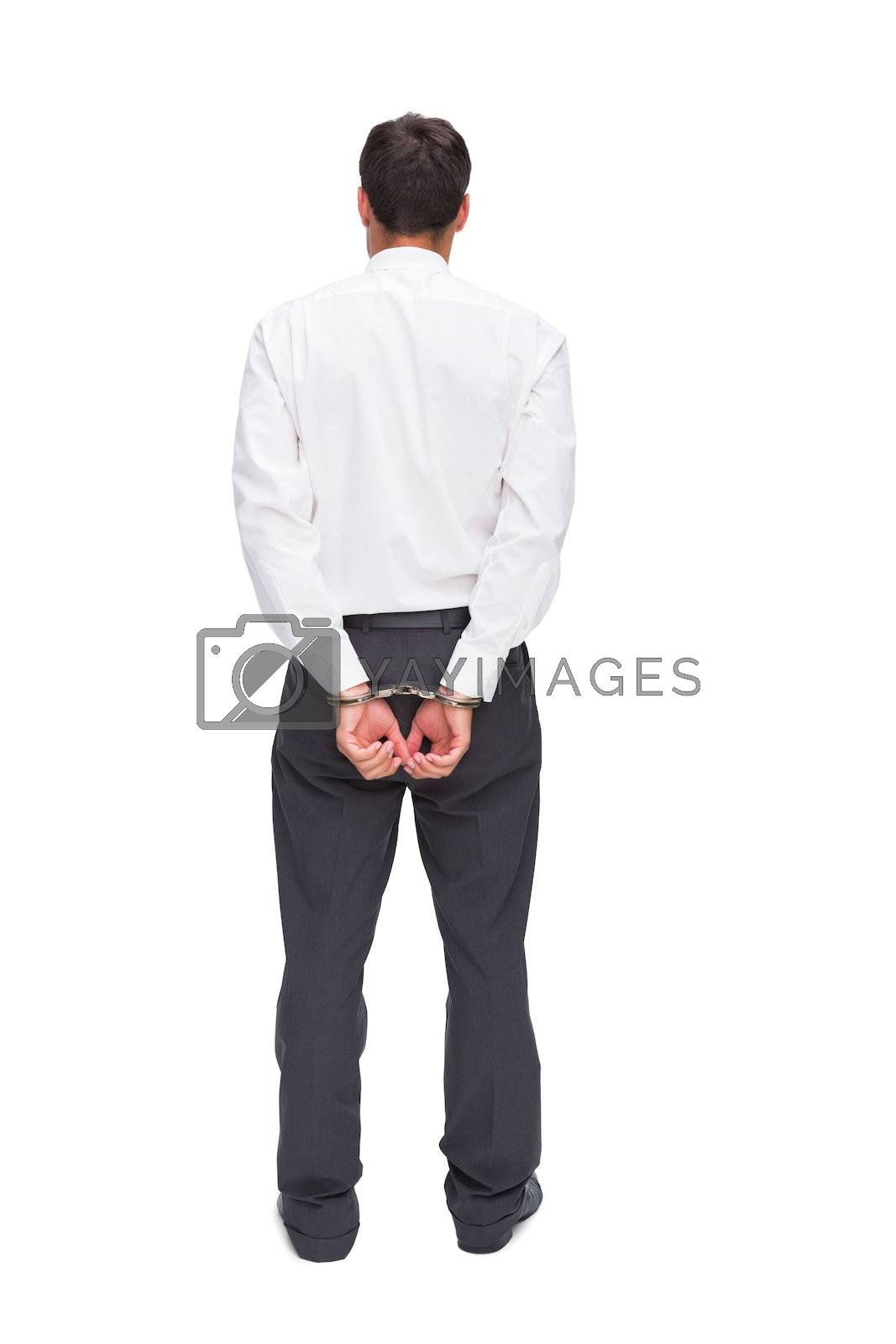 Rear view of young businessman wearing handcuffs by Wavebreakmedia