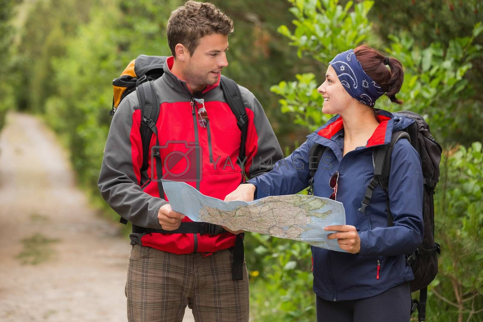 Smiling couple going on a hike together looking at map by Wavebreakmedia