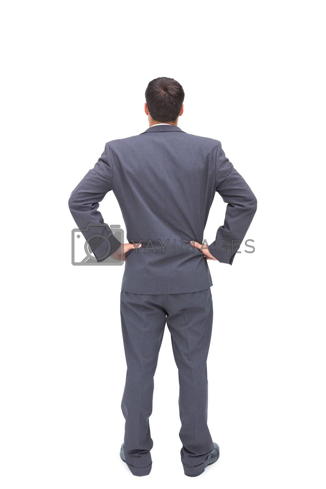 Businessman standing back to camera hands on hip  by Wavebreakmedia