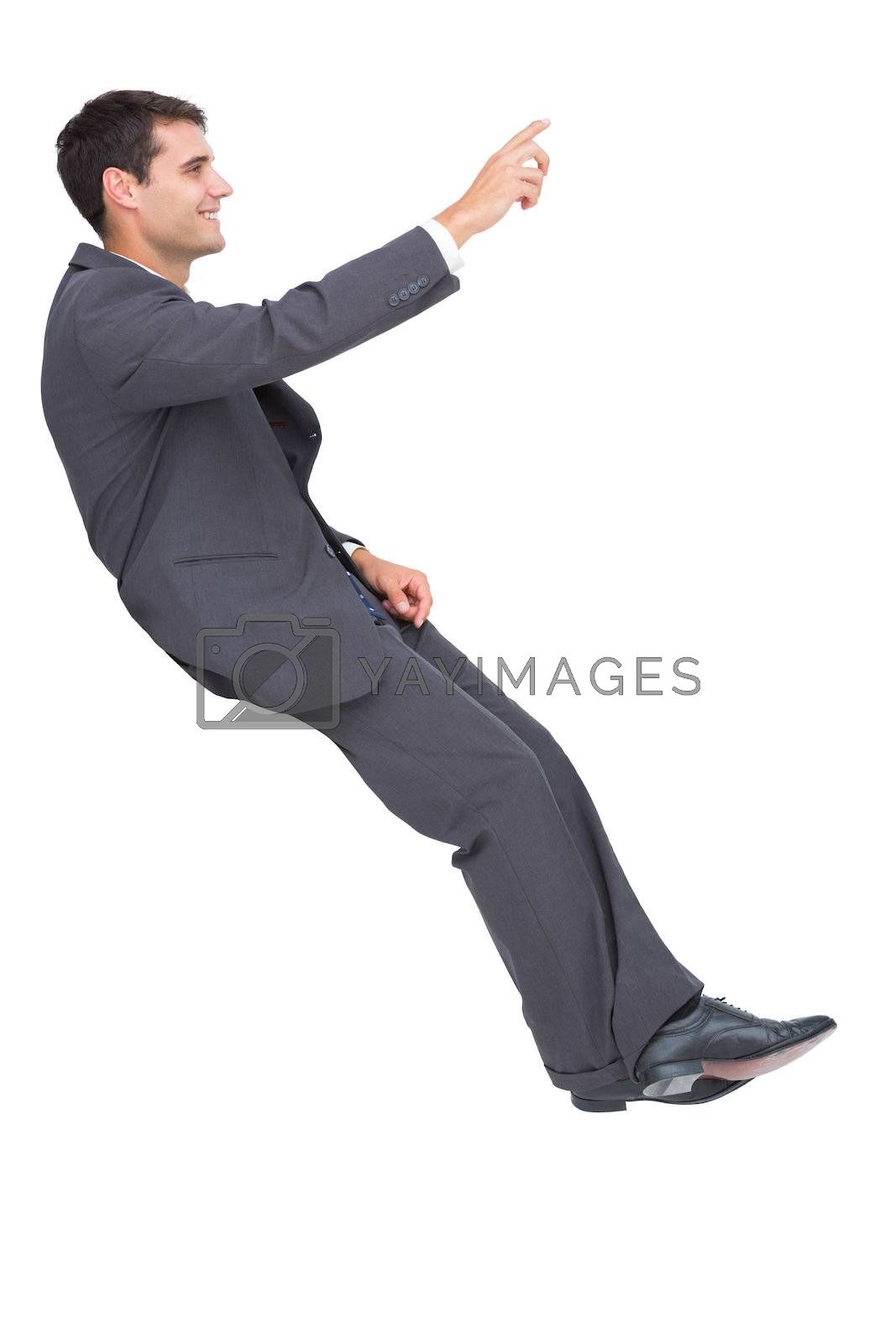 Smiling classy businessman sitting and pointing by Wavebreakmedia