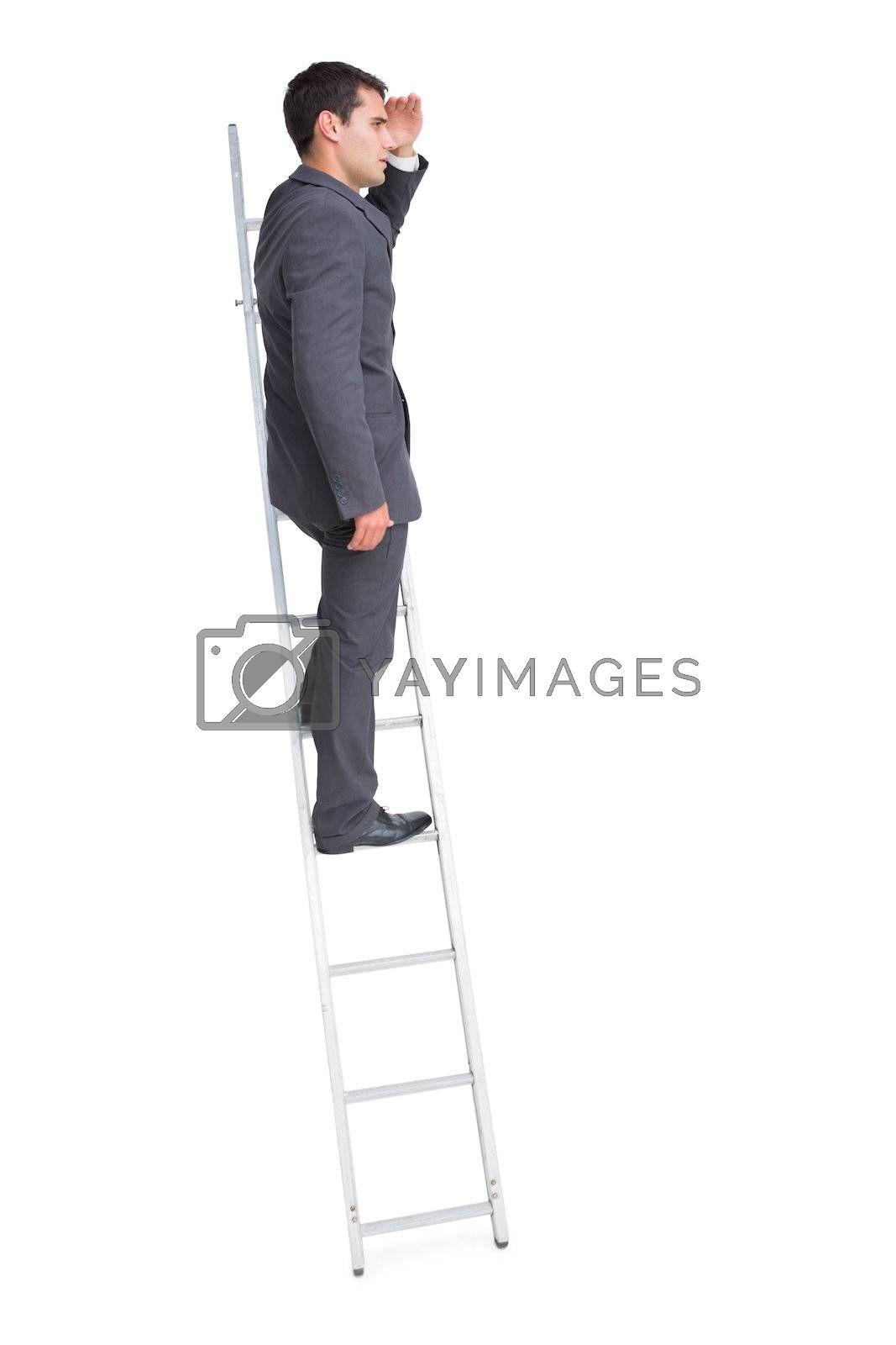 Young businessman standing on ladder looking away by Wavebreakmedia