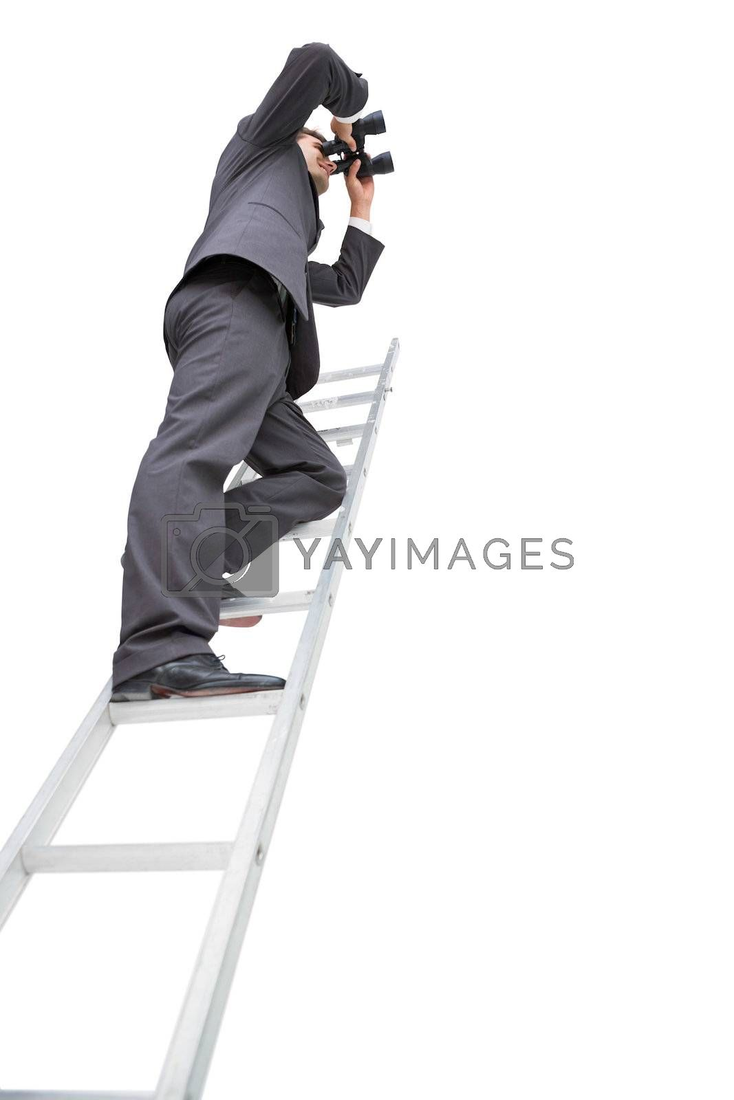 Low angle view of businessman standing on ladder using binoculars by Wavebreakmedia