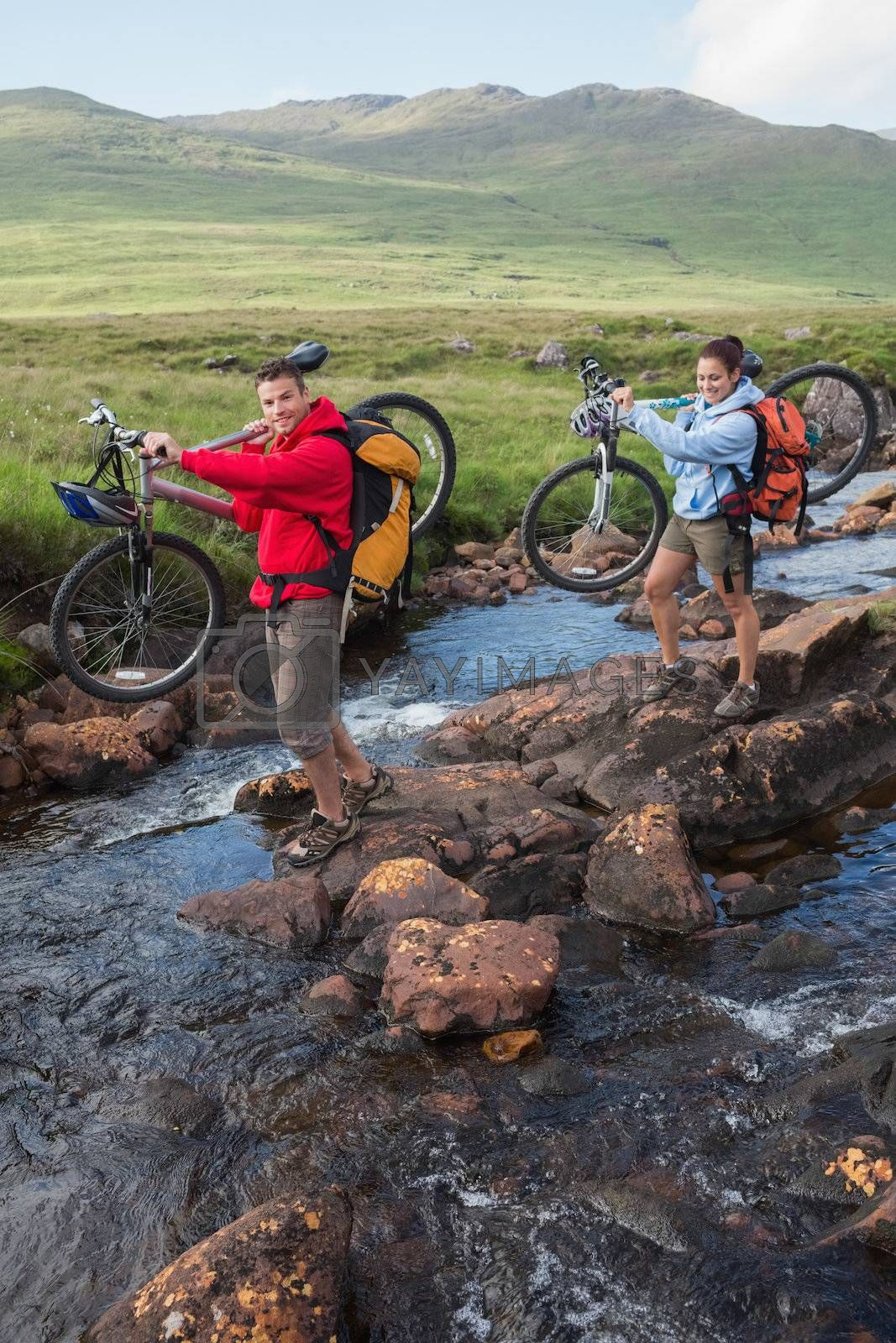 Couple crossing a stream holding their mountain bikes by Wavebreakmedia