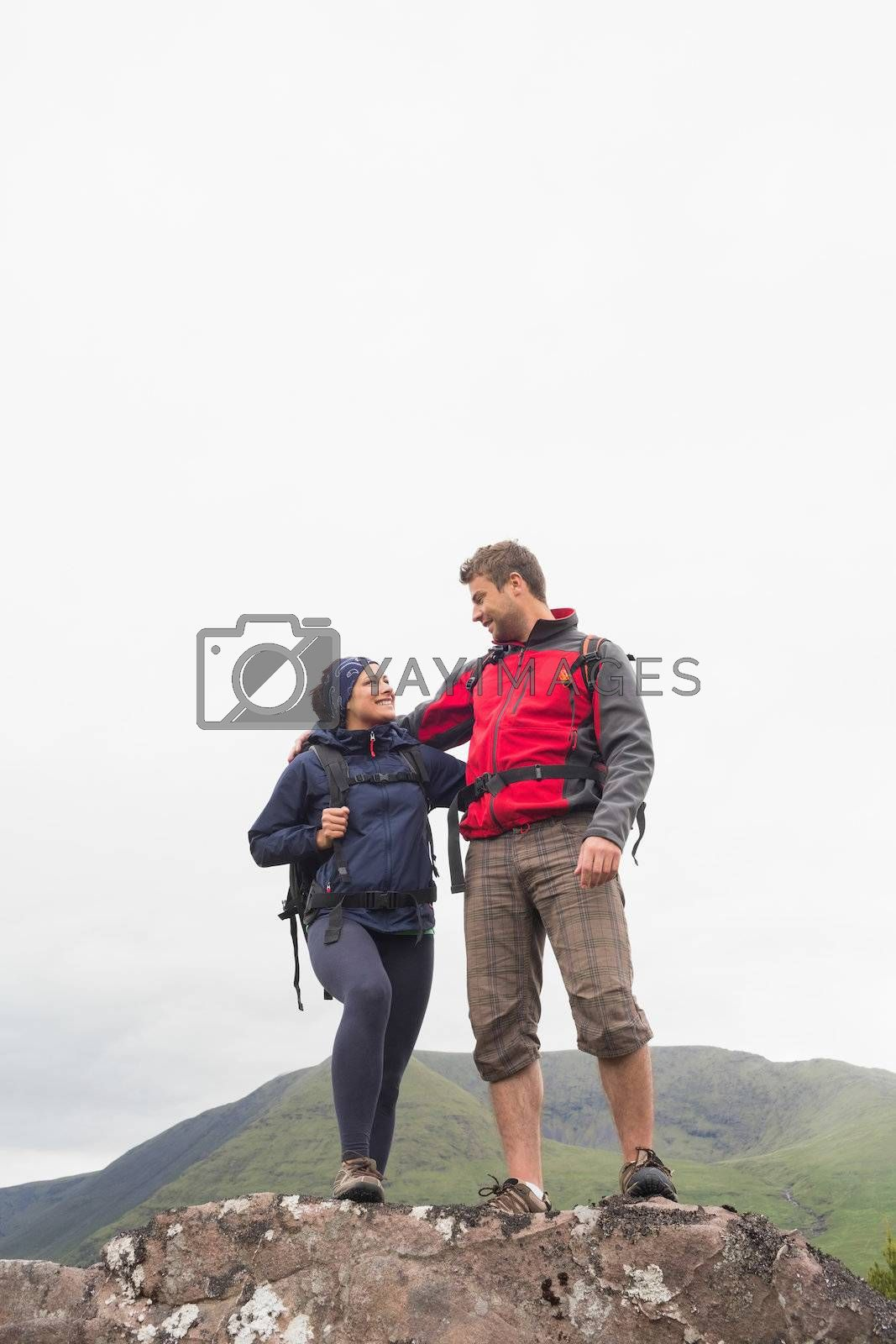 Couple standing on a rock embracing  by Wavebreakmedia