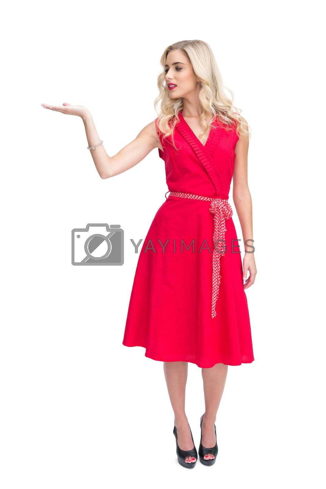 Smiling woman in red dress presenting something in her hand by Wavebreakmedia