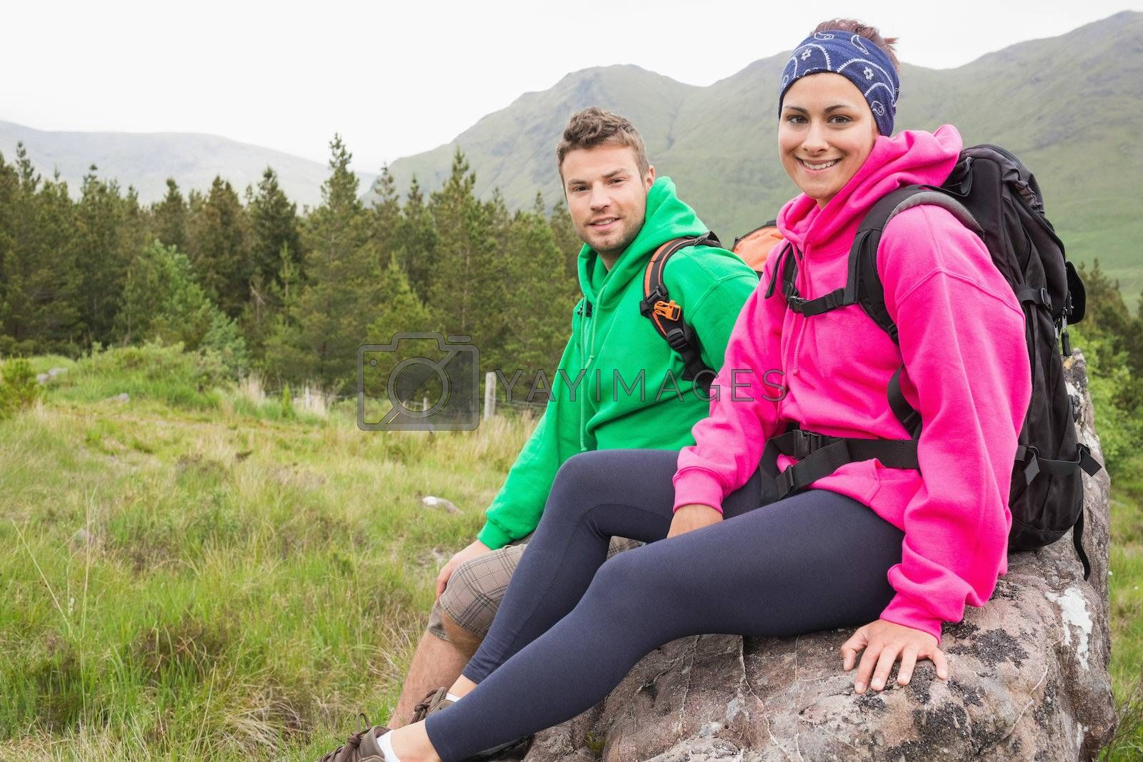 Couple sitting on a rock resting during hike by Wavebreakmedia