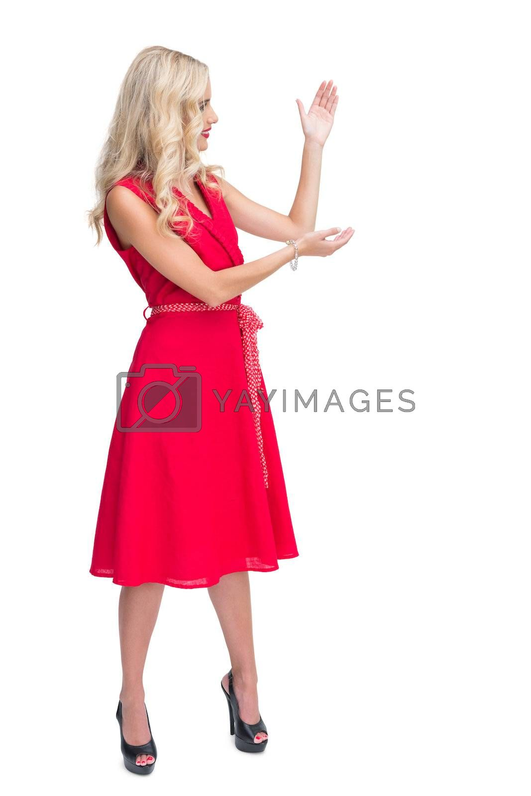 Smiling glamorous woman presenting something by Wavebreakmedia