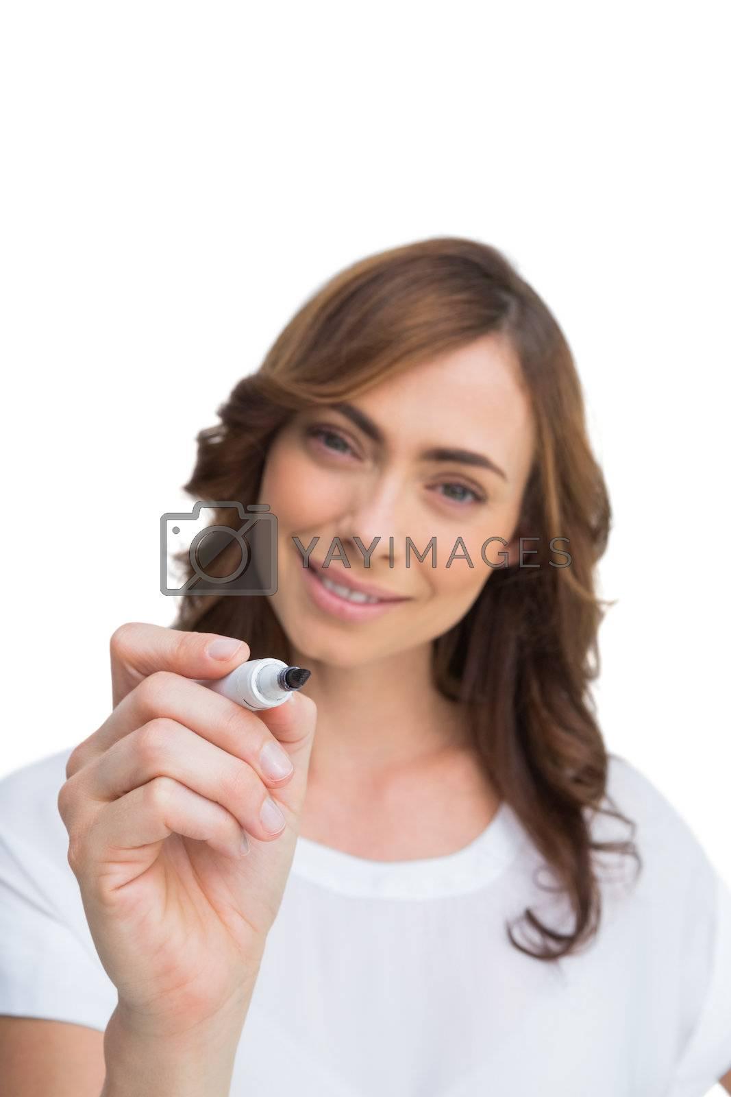 Smiling businesswoman holding whiteboard marker by Wavebreakmedia