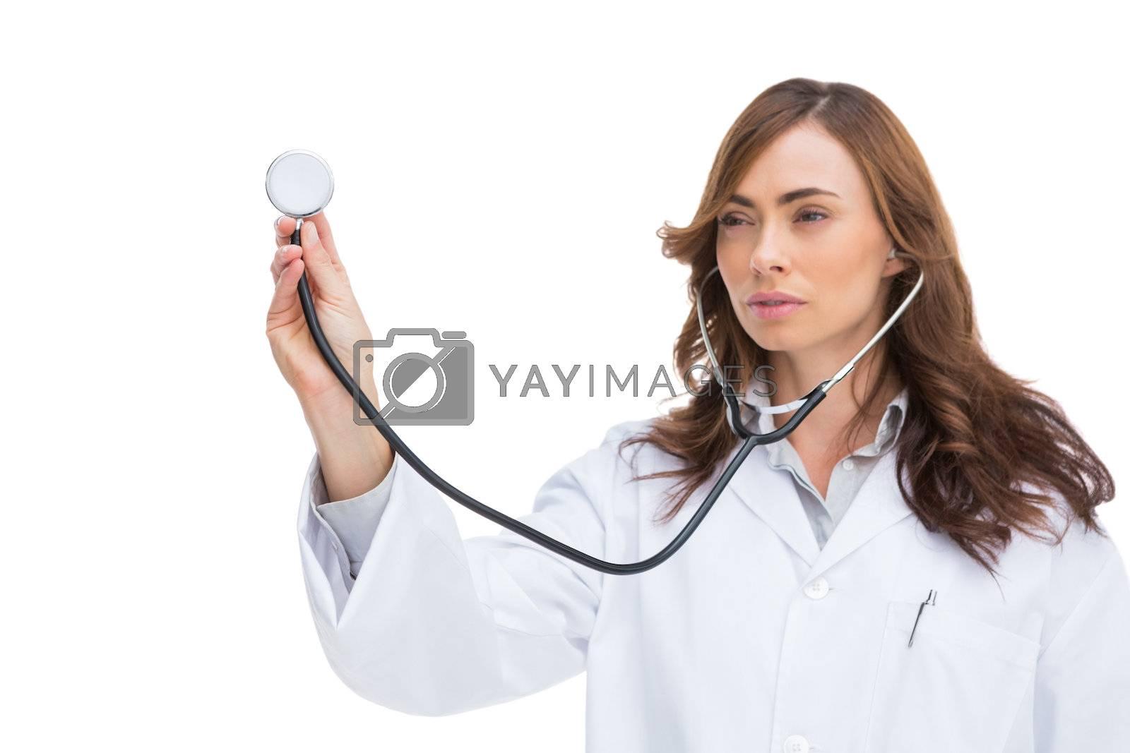 Serious pretty doctor holding stethoscope by Wavebreakmedia