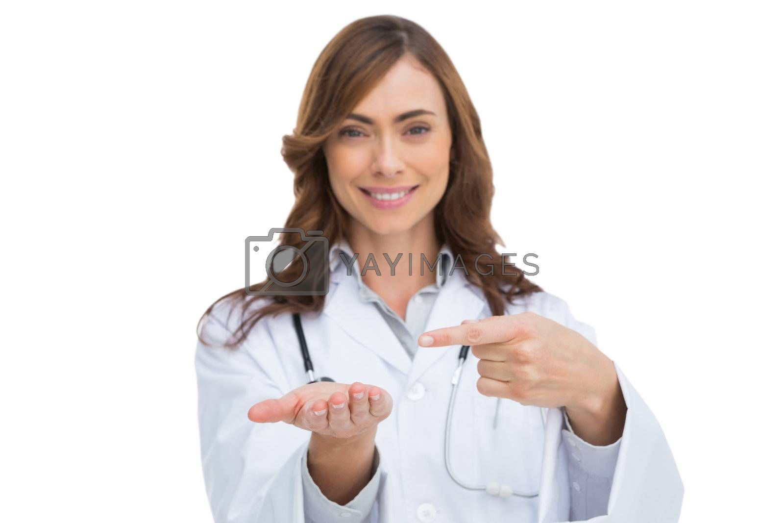 Smiling doctor pointing at something in her hand by Wavebreakmedia