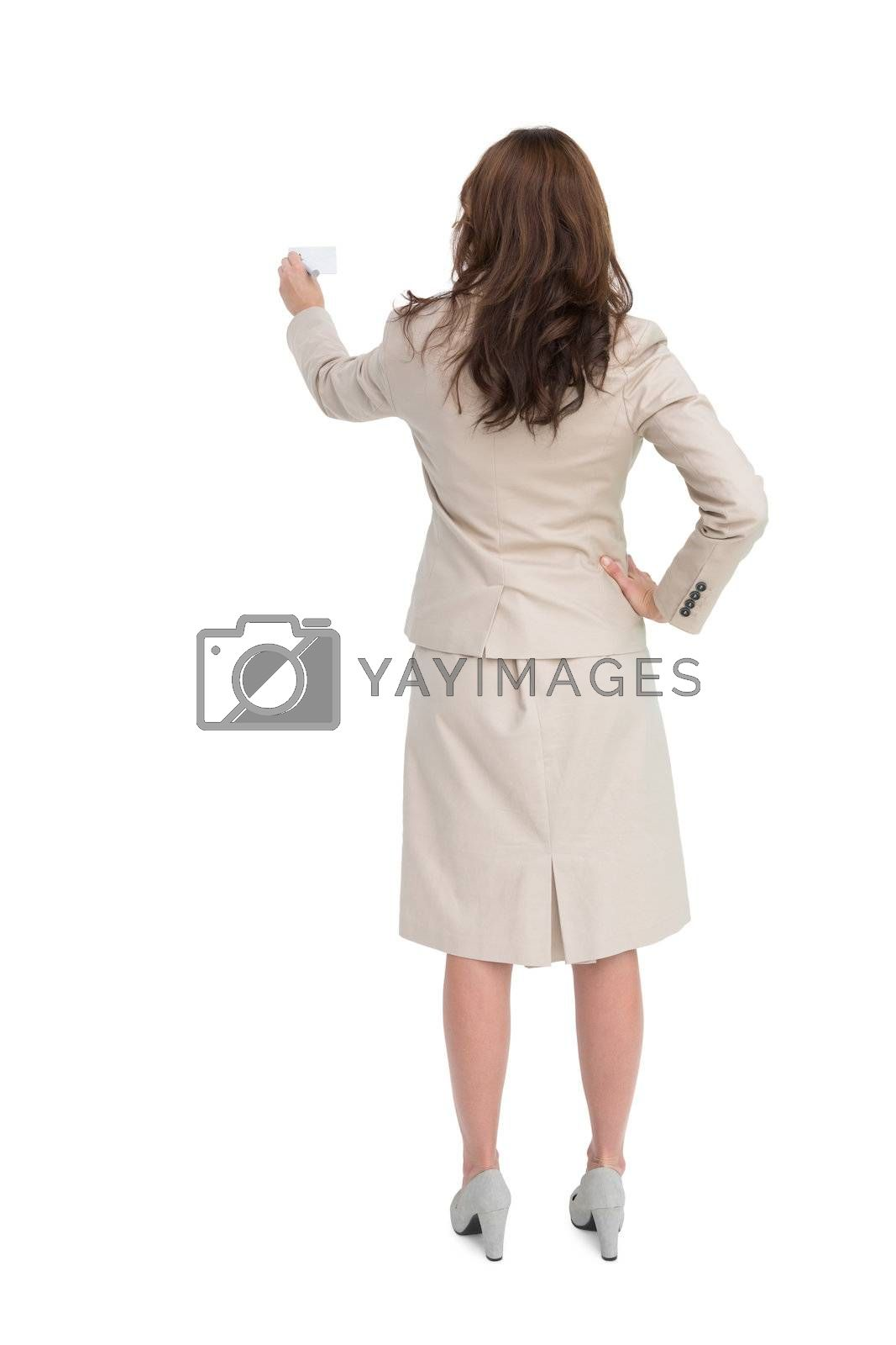 Businesswoman holding business card standing back to camera by Wavebreakmedia
