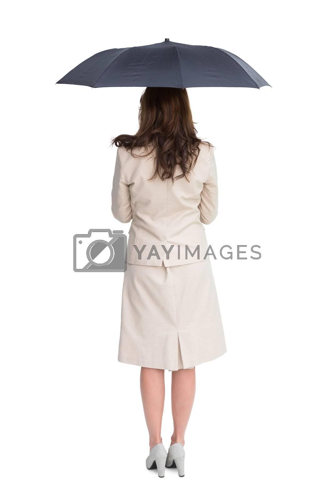 Rear view of classy businesswoman holding umbrella by Wavebreakmedia