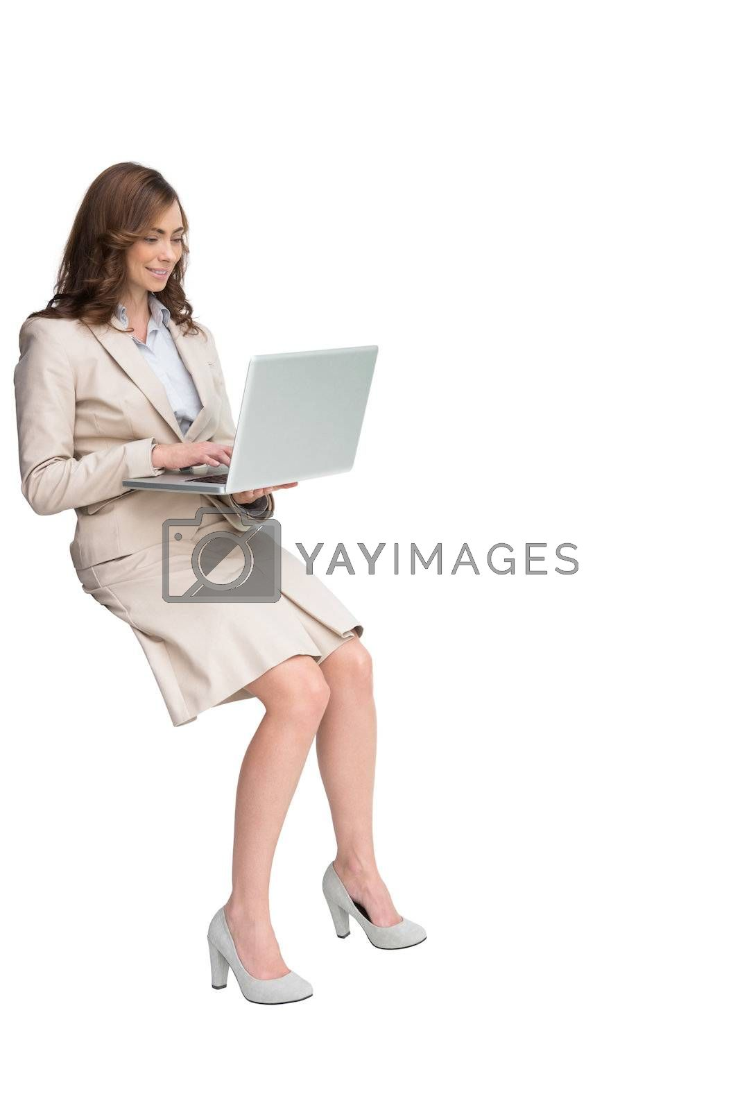 Smiling businesswoman sitting and using laptop by Wavebreakmedia