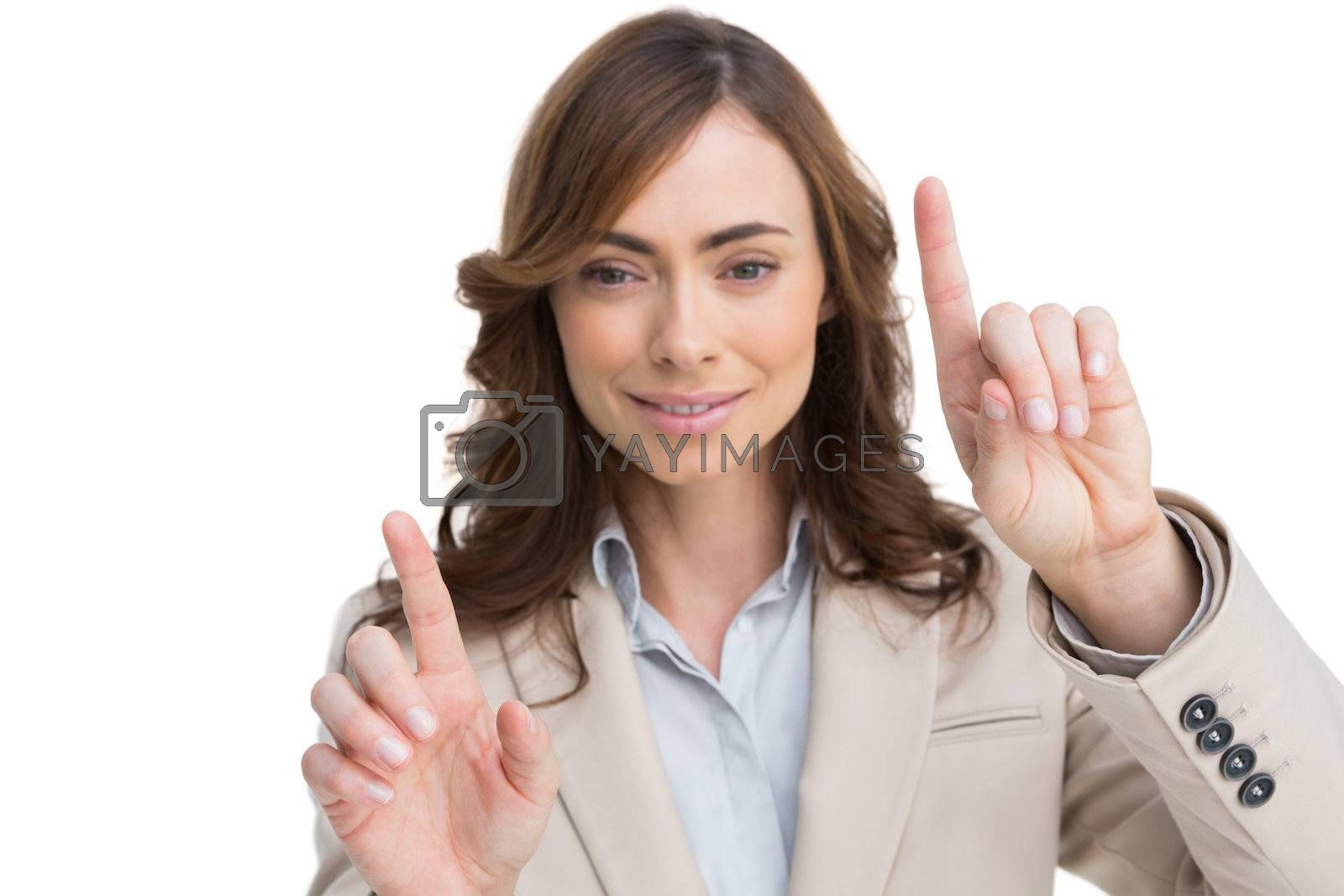 Classy businesswoman touching invisible screen by Wavebreakmedia