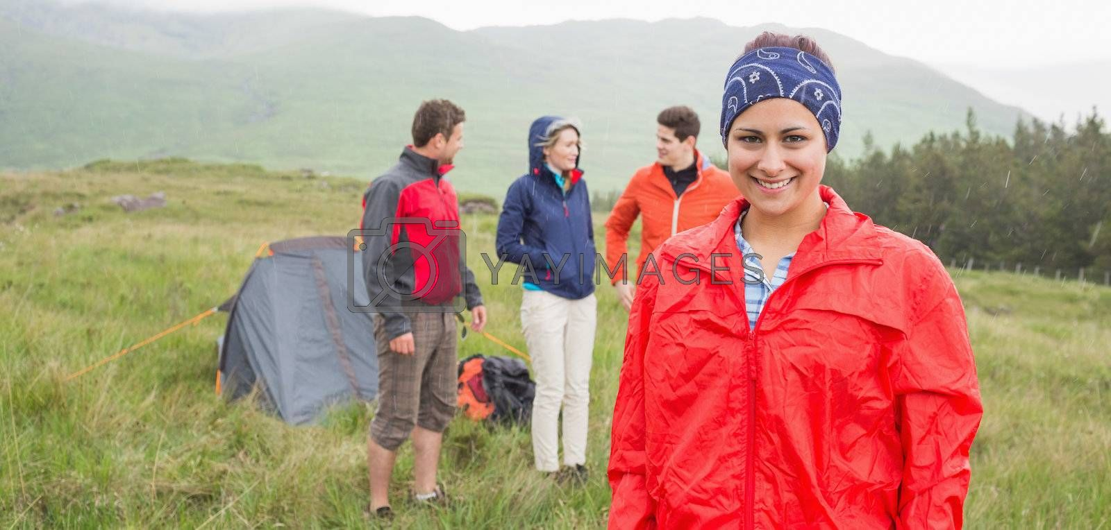 Brunette smiling at camera with friends behind her on camping trip by Wavebreakmedia