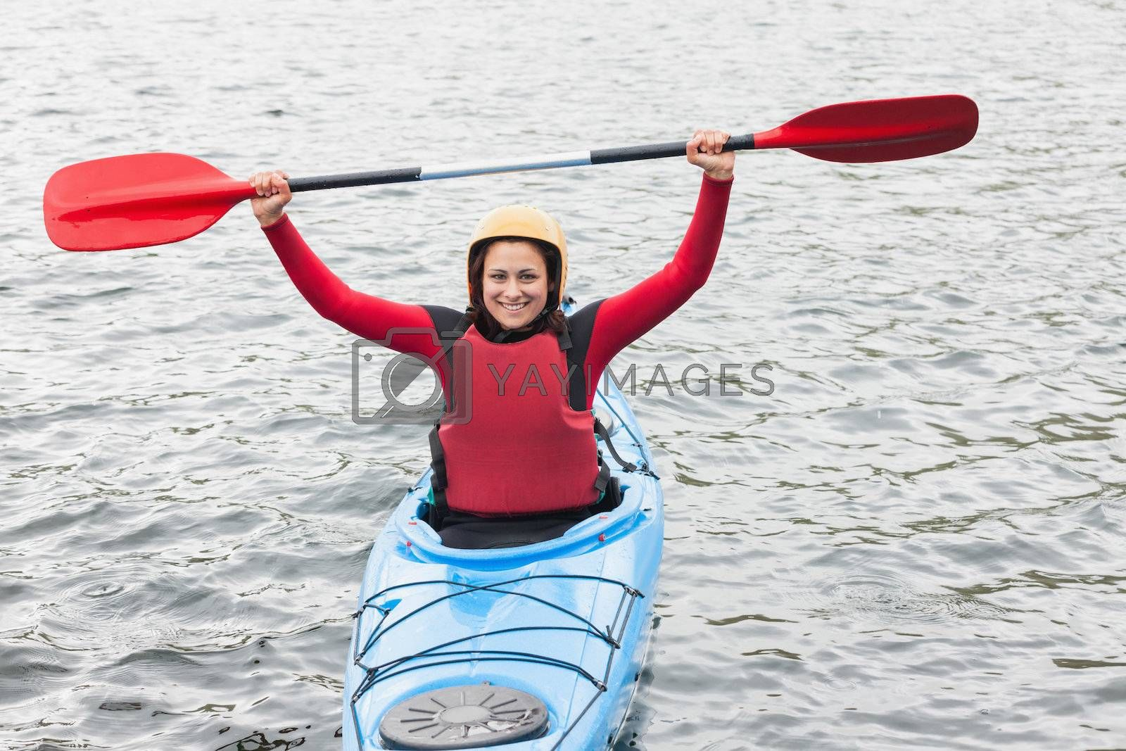 Smiling woman in a kayak cheering at the camera by Wavebreakmedia