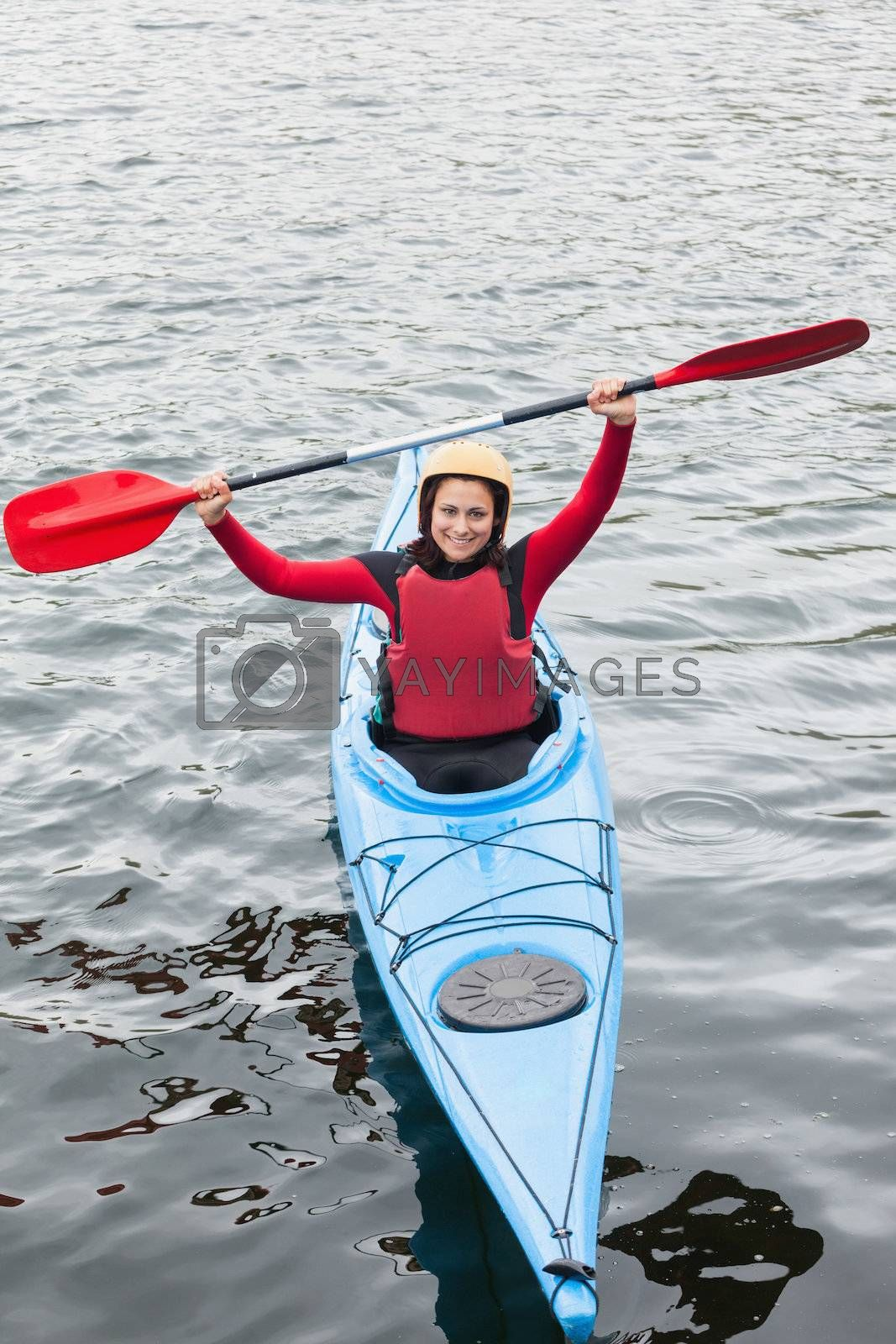 Happy woman in a kayak cheering at the camera by Wavebreakmedia