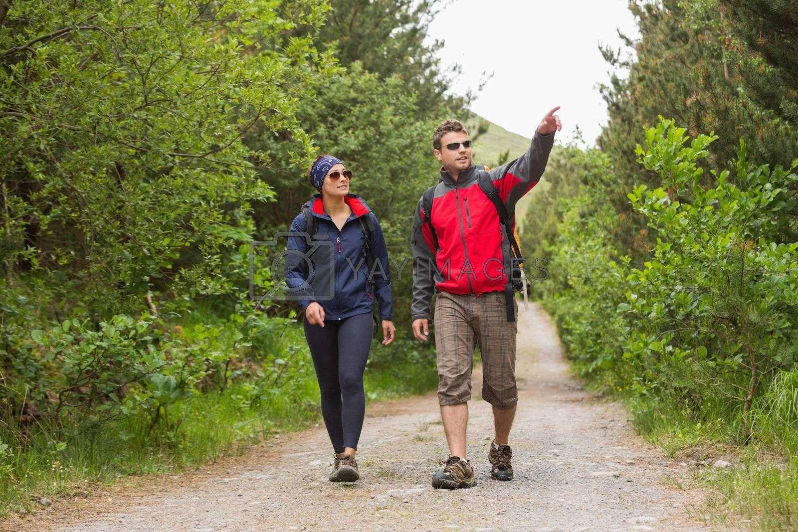 Couple going on a hike together with man pointing by Wavebreakmedia