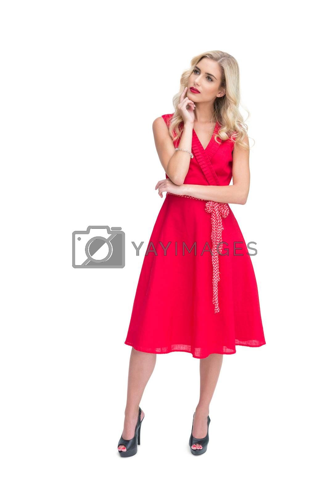 Thoughtful woman posing in red dress  by Wavebreakmedia