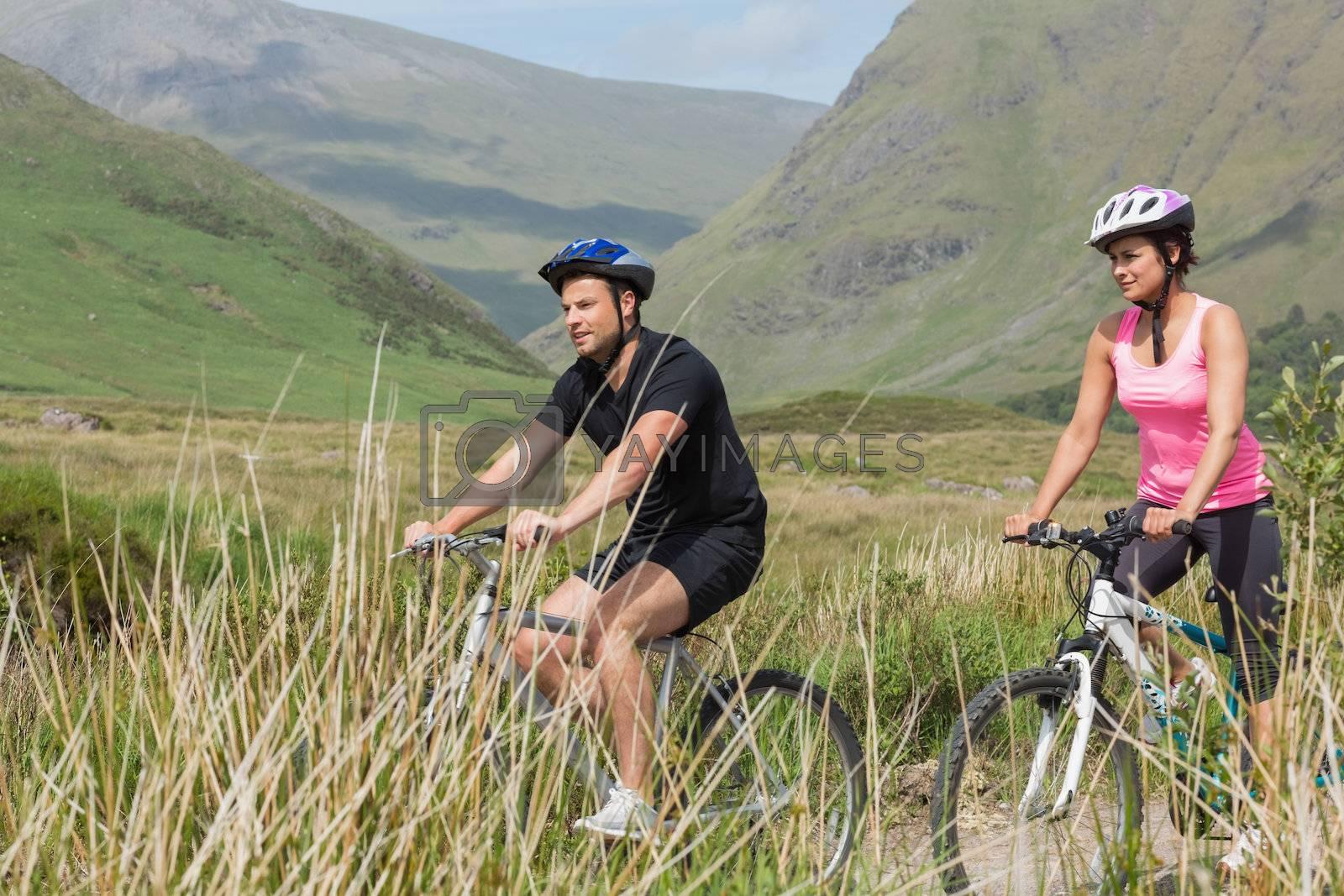 Athletic couple biking through countryside by Wavebreakmedia