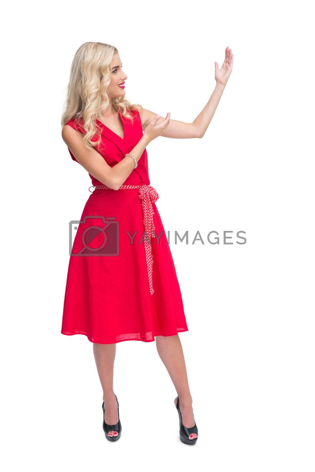 Glamorous blonde woman presenting something by Wavebreakmedia