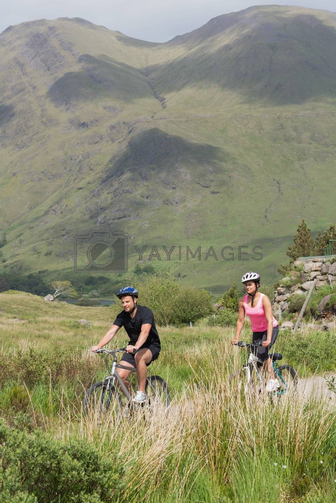 Athletic couple biking through wilderness by Wavebreakmedia