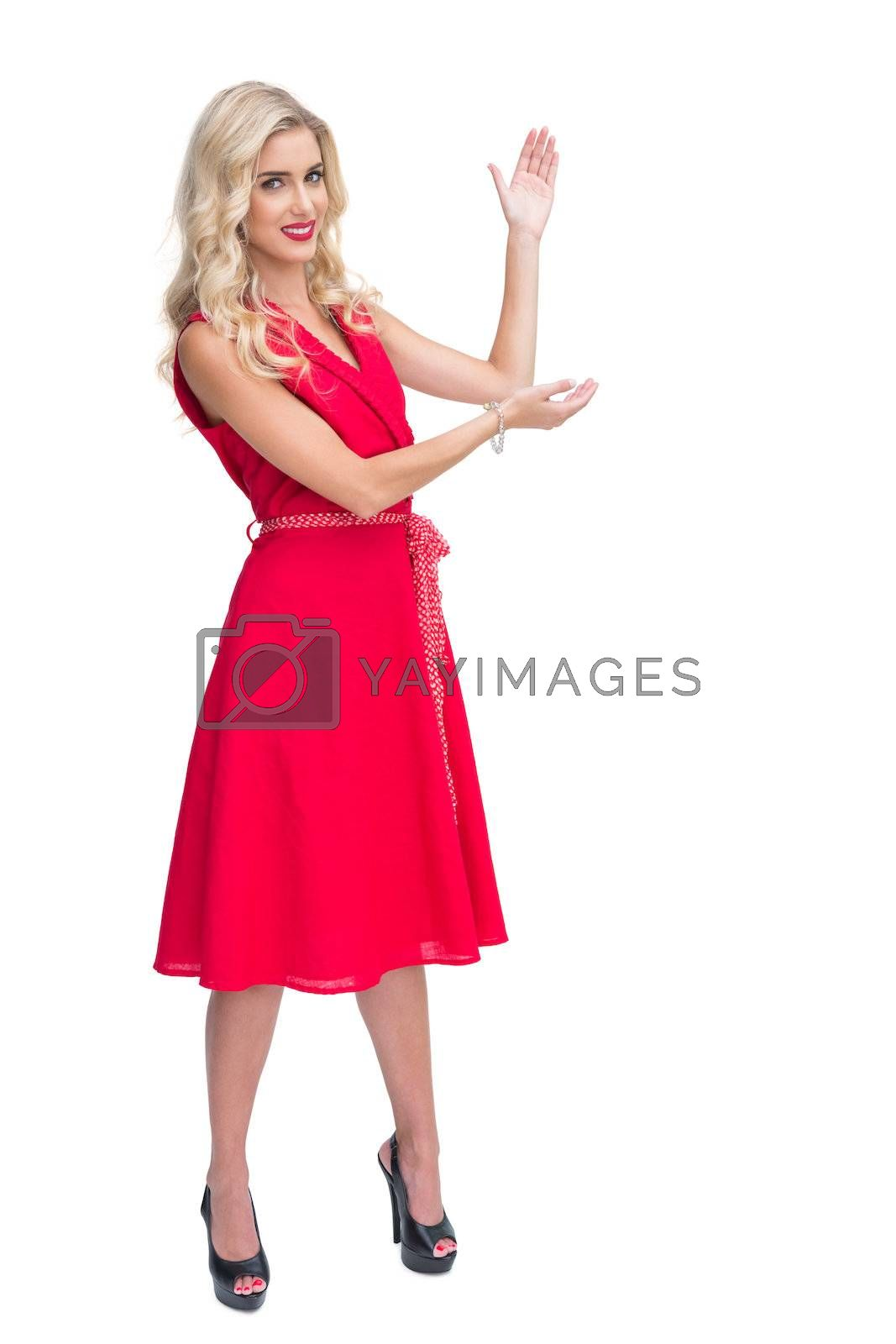 Woman wearing red dress presenting something by Wavebreakmedia