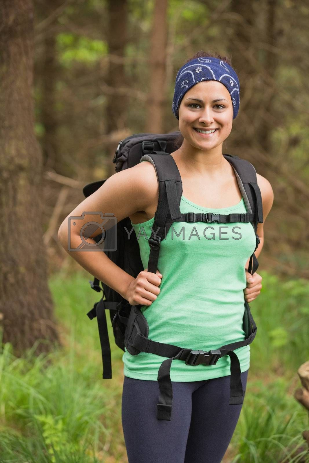 Pretty woman standing in a forest on hike by Wavebreakmedia