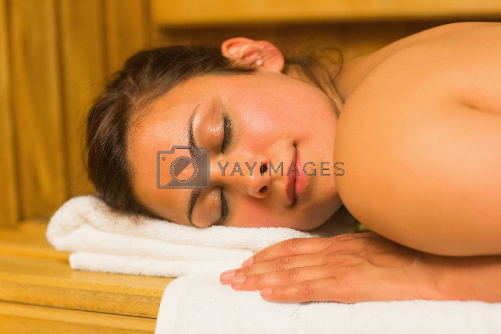 Smiling brunette lying down in a sauna by Wavebreakmedia