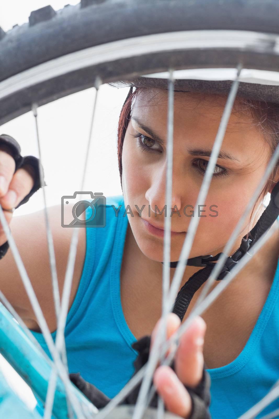 Athletic woman adjusting her spokes on bike wheel by Wavebreakmedia