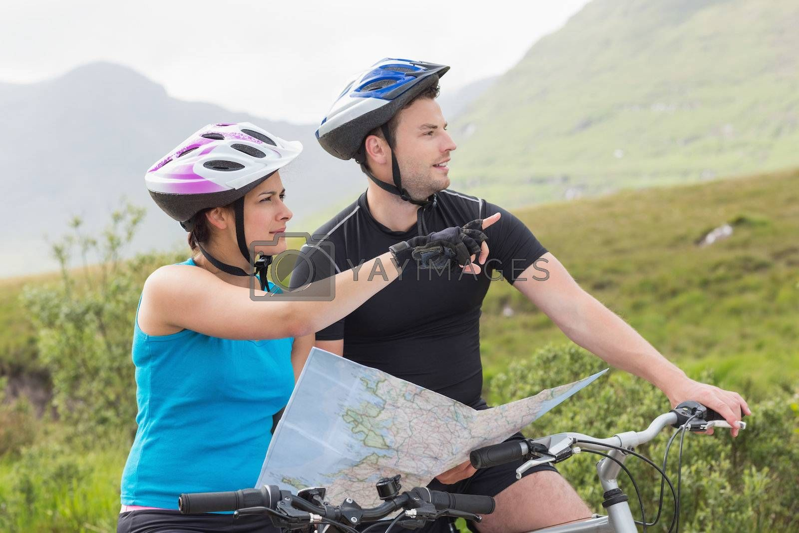 Couple on mountain bikes holding map and pointing by Wavebreakmedia