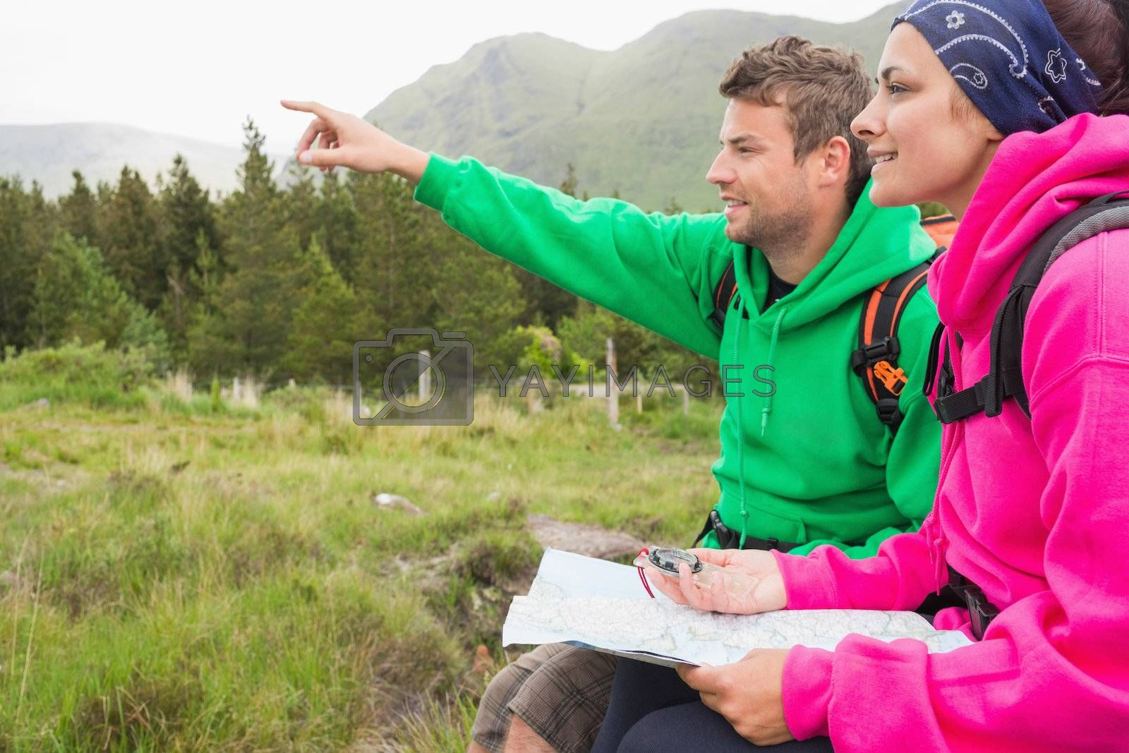 Couple sitting on a rock during hike using map and compass by Wavebreakmedia