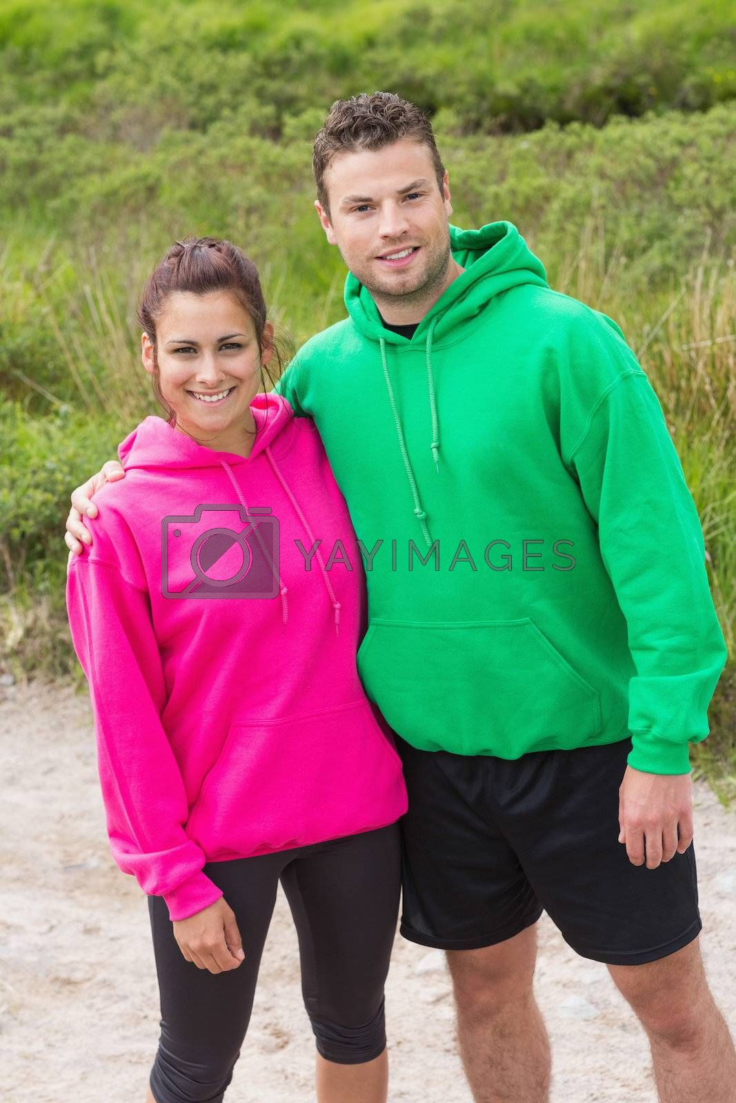 Athletic couple looking at camera and embracing by Wavebreakmedia