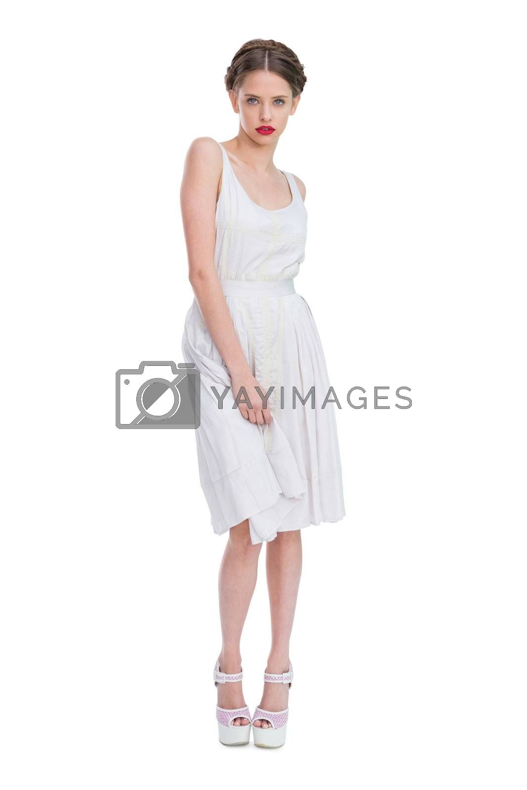 Attractive woman wearing white summer dress standing by Wavebreakmedia