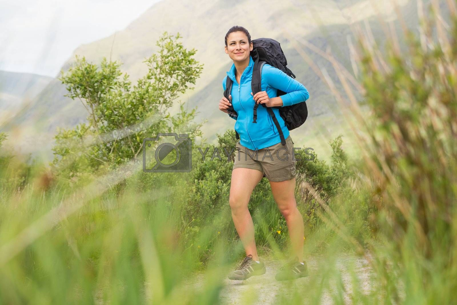 Female hiker with backpack walking and smiling by Wavebreakmedia
