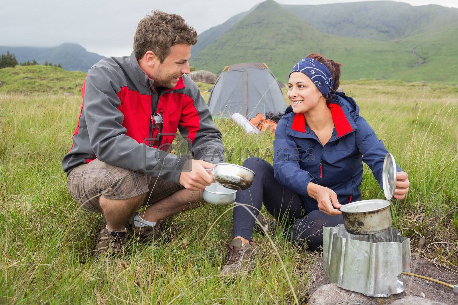 Couple cooking outside on camping trip and smiling by Wavebreakmedia