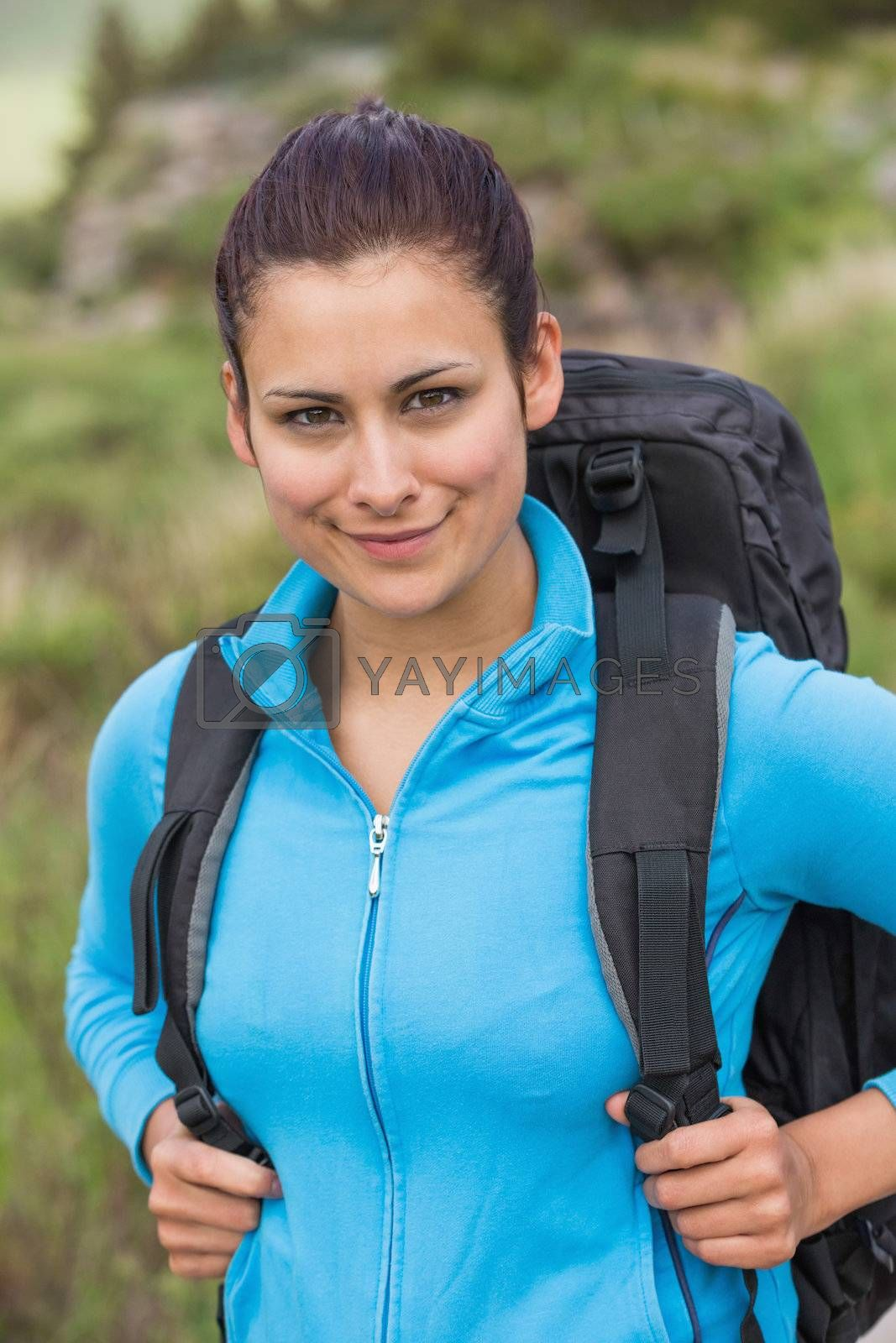 Smiling female hiker with backpack looking at camera by Wavebreakmedia