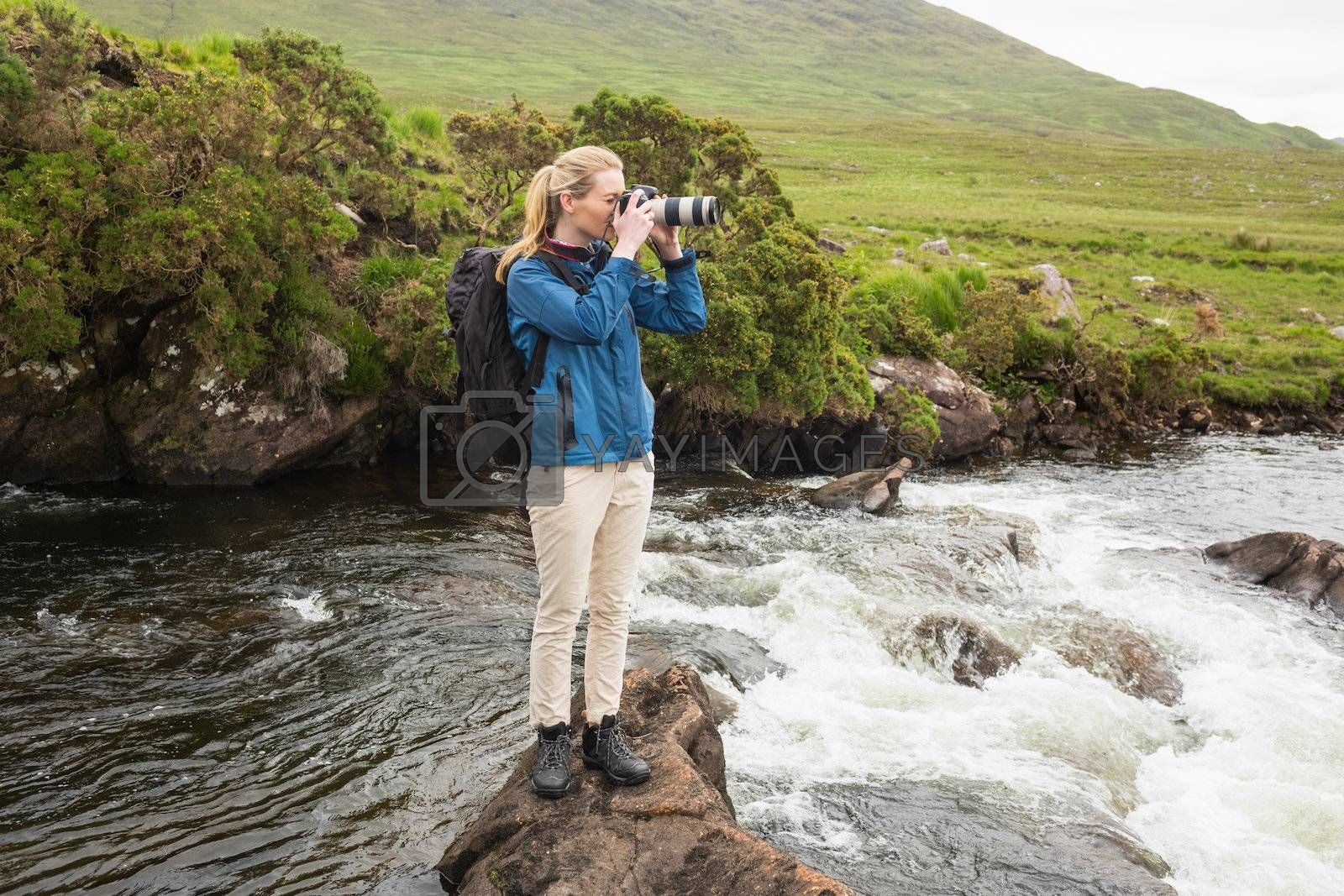 Blonde woman standing on a rock in a stream taking a photo by Wavebreakmedia