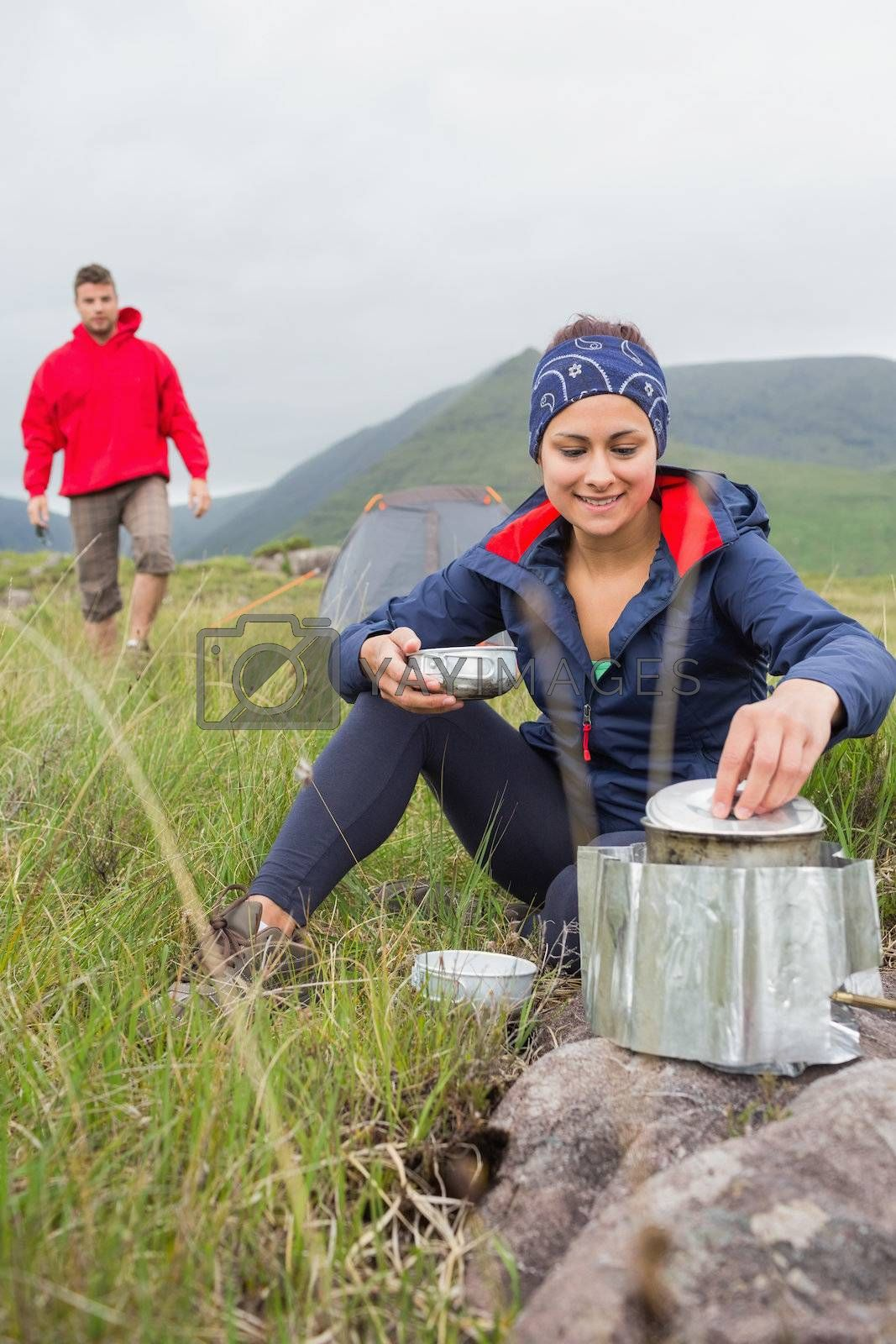Woman cooking outside on camping trip with boyfriend walking by Wavebreakmedia