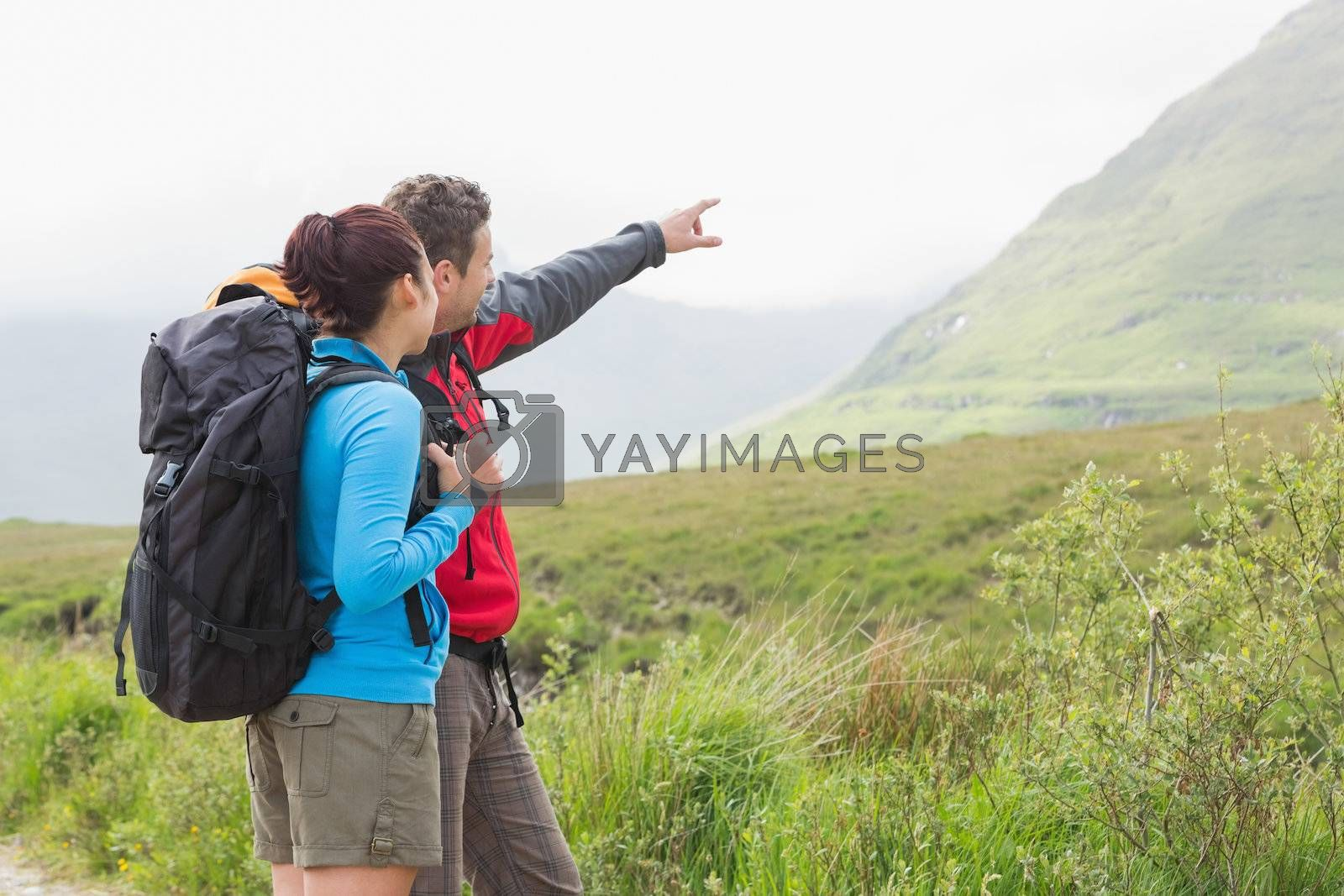 Couple of hikers with backpacks pointing at mountain by Wavebreakmedia