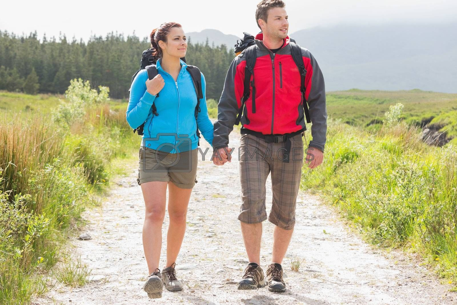 Hikers with backpacks holding hands and walking by Wavebreakmedia