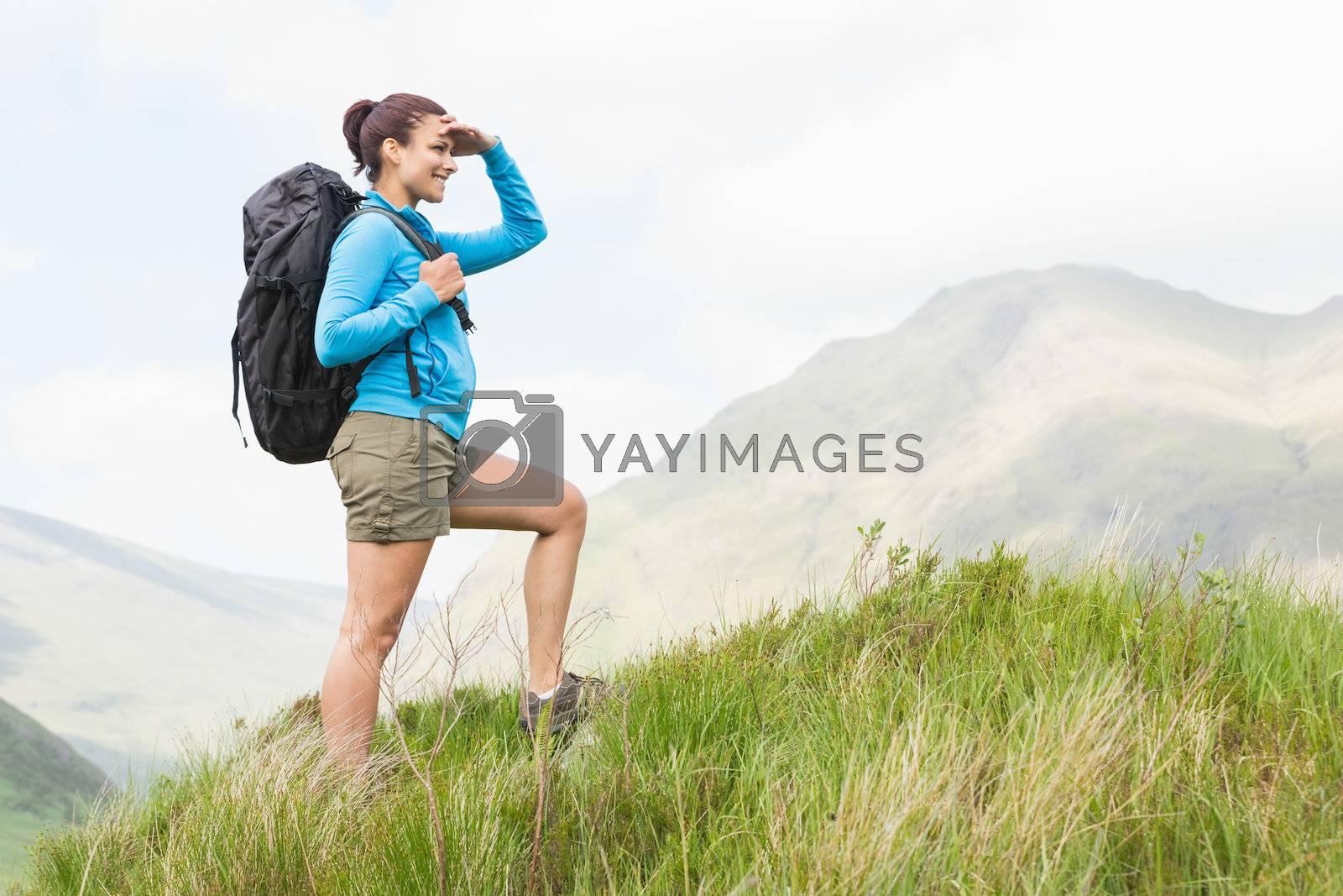 Pretty hiker with backpack walking uphill by Wavebreakmedia
