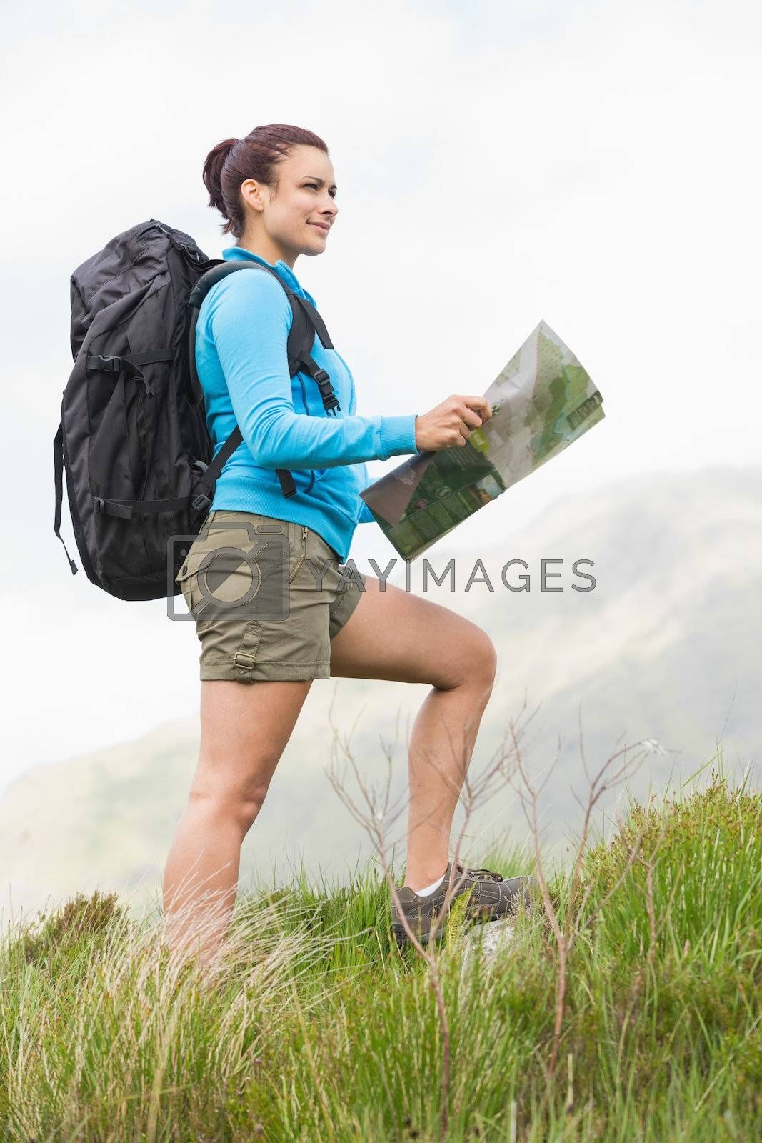 Attractive hiker with backpack walking uphill holding a map by Wavebreakmedia