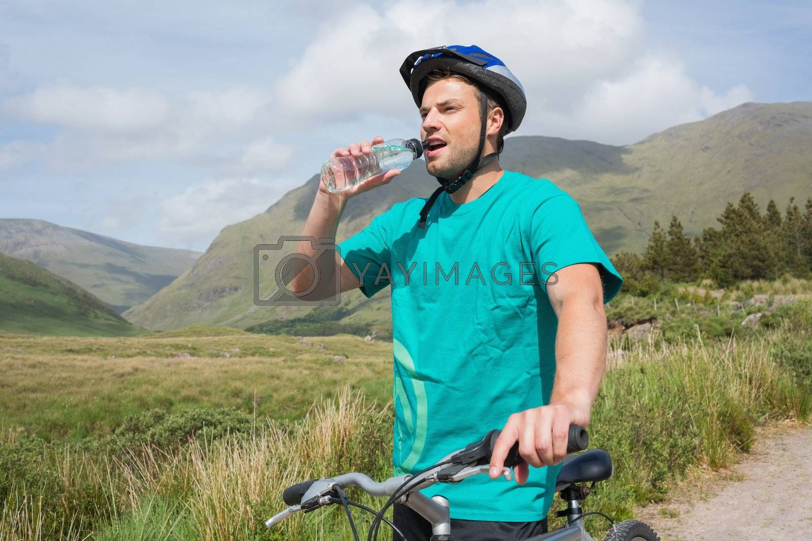 Fit man leaning on his mountain bike drinking water by Wavebreakmedia