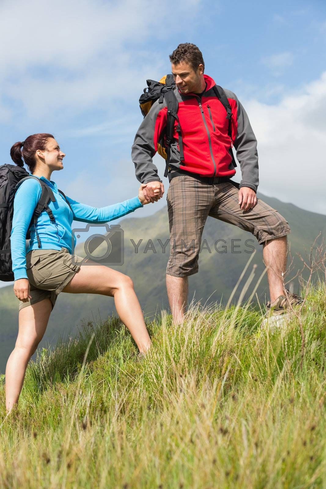 Handsome hiker helping his girlfriend uphill by Wavebreakmedia