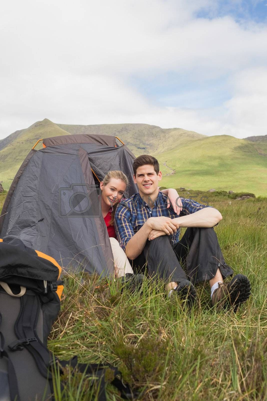 Happy couple sitting in their tent after a hike and looking  by Wavebreakmedia